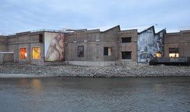 Stary przemysłowy budynek wzdłuż rzeki zdjęcia royalty free