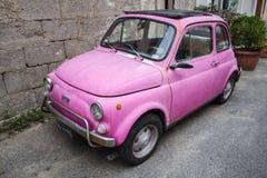 Stary różowy Fiat Nuova 500 miasta samochód Obrazy Stock
