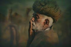 Stary Rajasthani mężczyzna przeciw tłu jego wielbłądy Zdjęcia Royalty Free