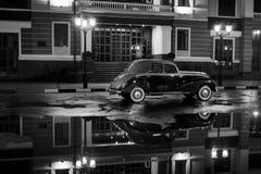 Stary retro samochodu pobyt na asfaltowej miasto drodze przy dżdżystą nocą obraz stock