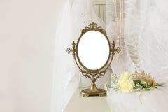 Stary rocznika owalu lustro, piękna biała ślubna suknia i przesłona na krześle obrazy stock