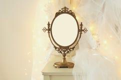 Stary rocznika owalu lustro, piękna biała ślubna suknia i przesłona na krześle z złocistą girlandą zaświecamy fotografia royalty free