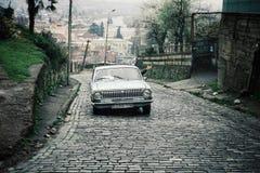stary rosyjski samochód używać jako prowizoryczny taxi wspina się strome wzgórze ulicy miasto z klientami wśrodku fotografia royalty free
