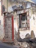 stary rujnujący dom częsciowo załamywał się na połogiej ulicie z blokuję w górę drzwiowych rozdrabnianie ścian i fading czerwień  zdjęcia royalty free