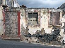 Stary rujnujący dom częsciowo załamywał się na połogiej ulicie z blokuję w górę drzwiowych rozdrabnianie ścian i fading czerwień  zdjęcie stock