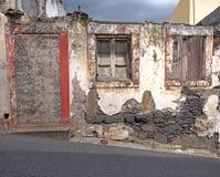 stary rujnujący dom częsciowo załamywał się na ulicie z blokuję w górę drzwiowych rozdrabnianie ścian i fading czerwień malował o zdjęcia stock