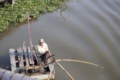Stary rybak unosi się na rzece i łowi z siecią Zdjęcia Stock