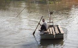 Stary rybak unosi się na rzece i łowi z siecią Zdjęcie Stock