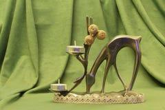 Stary rzadki metalu posążek rogacze w postaci candlestick z wosk świeczkami i dekoracyjnymi złotymi jabłkami na zielonej tkaninie obraz stock