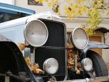 Stary samochód w jardzie który zakrywa z żółtymi liśćmi klonowymi zdjęcia royalty free