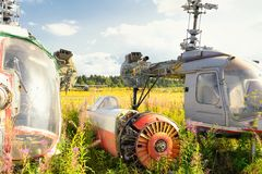 Stary samolotowy kadłub i ośniedziali helikoptery na zielonej trawie Zdjęcia Royalty Free