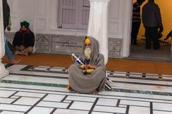 Stary sikhijczyk w tradycyjnej sukni siedzi w podwórzu Złota świątynia i trzyma starego kordzika obraz stock
