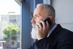 Stary sir opowiada na telefonie z popielatą brodą podczas gdy przyglądający windo out Obraz Stock