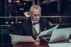 Stary skoncentrowany biznesmen patrzeje grafika fotografia stock