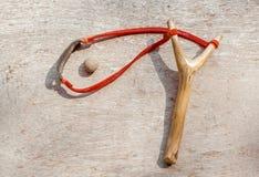 Stary slingshot i gliny wyrko na starym drewnianym tle Zdjęcie Royalty Free