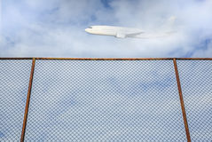 Stary stali ogrodzenie z płaskim lataniem w niebie Fotografia Stock