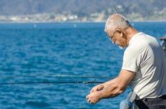 Stary starzejący się mężczyzna łowi z mola Obrazy Royalty Free