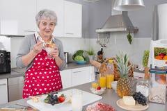 Stary szczęśliwy kobiety łasowania jogurt w ranku obrazy royalty free