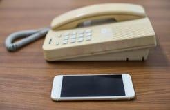 Stary telefon i wisząca ozdoba, pojęcia porównujemy nowego i starego technologi Zdjęcia Royalty Free