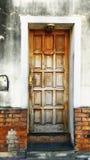 Stary wietrzejący drewniany drzwi na ścianie z cegieł obrazy royalty free