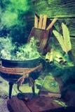 Stary witcher kocioł z zieleń dymem i książki dla Halloween Zdjęcia Stock