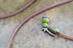 Stary wodnej kiści pistolet i wąż elastyczny na cement ziemi Zdjęcie Stock