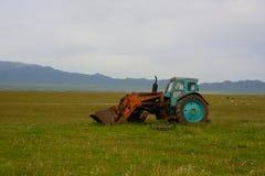 Stary zaniechany kołowy ciągnik na zielonym polu Fotografia Royalty Free