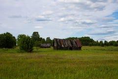 Stary zawalony drewniany dom na zielonym polu obraz stock