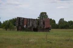 Stary zawalony drewniany dom na zielonym polu zdjęcie royalty free