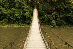 Stary zawieszenie most krzyżuje halną rzekę fotografia royalty free