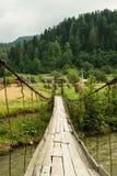 Stary zawieszenie mosta góry rzeki skrzyżowanie Krajobrazowy widok zdjęcia stock