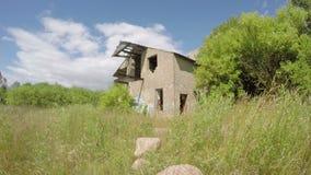 Stary zdewastowany budynek w zielonej łące na wietrznym dniu, czasu upływ 4 k zbiory wideo