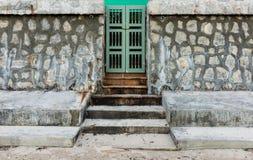 Stary zielony drzwi i kamienna ściana Zdjęcia Stock