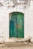 Stary zielony szalunku drzwi w scuffed ścianie Fotografia Stock
