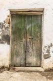 Stary zielony szalunku drzwi w scuffed ścianie Zdjęcie Stock