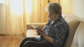 Starych kobiet spojrzenia przy obrazkami używać cyfrową pastylkę zbiory