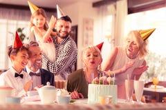 Starzeć się kobiet podmuchowe świeczki podczas gdy świętujący urodziny zdjęcia stock