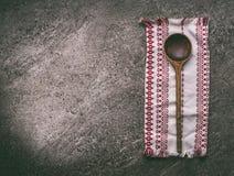 Starzejąca się drewniana łyżka z kuchenną pieluchą na wieśniaka kamienia kuchennym stole, odgórny widok Krajowy kuchni jedzenie i zdjęcia royalty free