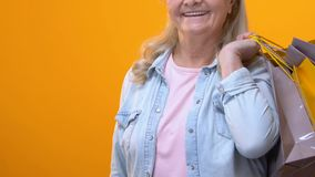 Starzejąca się kobieta trzyma euro banknoty w ręce z torbami na zakupy, zakupu rabat zdjęcie wideo