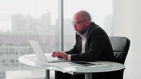 Starzejący się biznesmen w kostiumu używać komputerowy okno w nowożytnym białym biurze z panoramicznymi okno blisko zbiory wideo