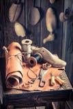 Starzejący się cobbler miejsce pracy z butami, koronkami i narzędziami, obrazy royalty free