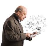 Starzejący się czyta książki z pastylką zdjęcia royalty free