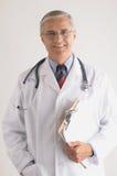 starzejący się deskowy klamerki lekarki mienia środek Obraz Stock