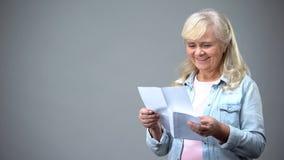 Starzejący się emeryt damy czytelniczy list od dzieci otrzymywa dobre wieści pożyczkowego zatwierdzenie obrazy stock