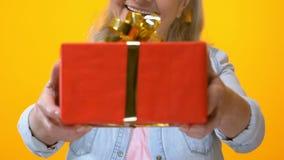 Starzejący się kobieta seans teraźniejszy na żółtym tle, urodzinowy prezent, rocznica zbiory wideo