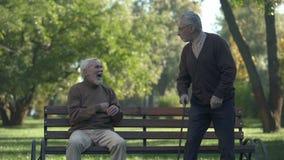 Starzejący się mężczyzna żartuje z przyjaciela kopania kruponem, przyjaźń humor, mieć zabawę, czas wolny zdjęcie wideo