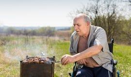 Starzejący się mężczyzna na jego wózka inwalidzkiego opieczeniu Pod słońcem Obraz Stock