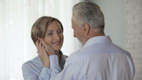 Starzejący się męski cupping kobieta policzek stawia jego czoło przeciw jej, kochający uczucia zdjęcie wideo