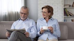 Starzejący się pary obsiadanie na kanapy i gawędzenie mężczyzny mienia gazetowej damie pije herbaty fotografia royalty free