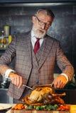 Starzejący się przystojny mężczyzna w formalnym drogim kostiumu tnącym za piec kurczaku zdjęcie stock
